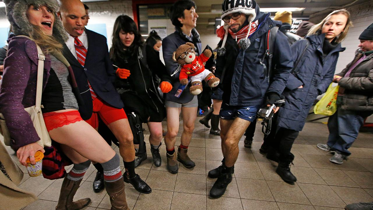 A passerby glances as participants in the annual No Pants Subway Ride pose in their underwear, Jan. 8, 2017, in New York after riding the subway pantless. (AP Photo/Kathy Willens)