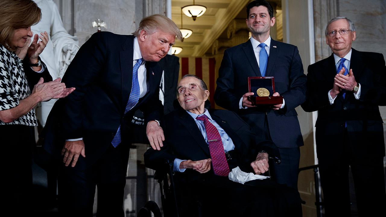 President Donald Trump congratulates former Sen. Bob Dole during a ceremony to award him the Congressional Gold Medal on Capitol Hill.  (AP Photo/Evan Vucci)