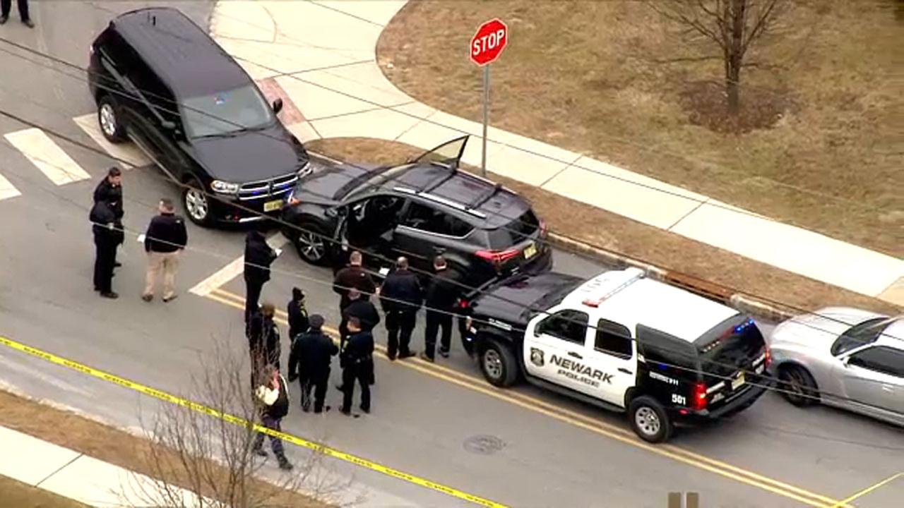 Newark police and New Jersey State Troopers surround the suspected vehicle in a Newark, New Jersey homicide.