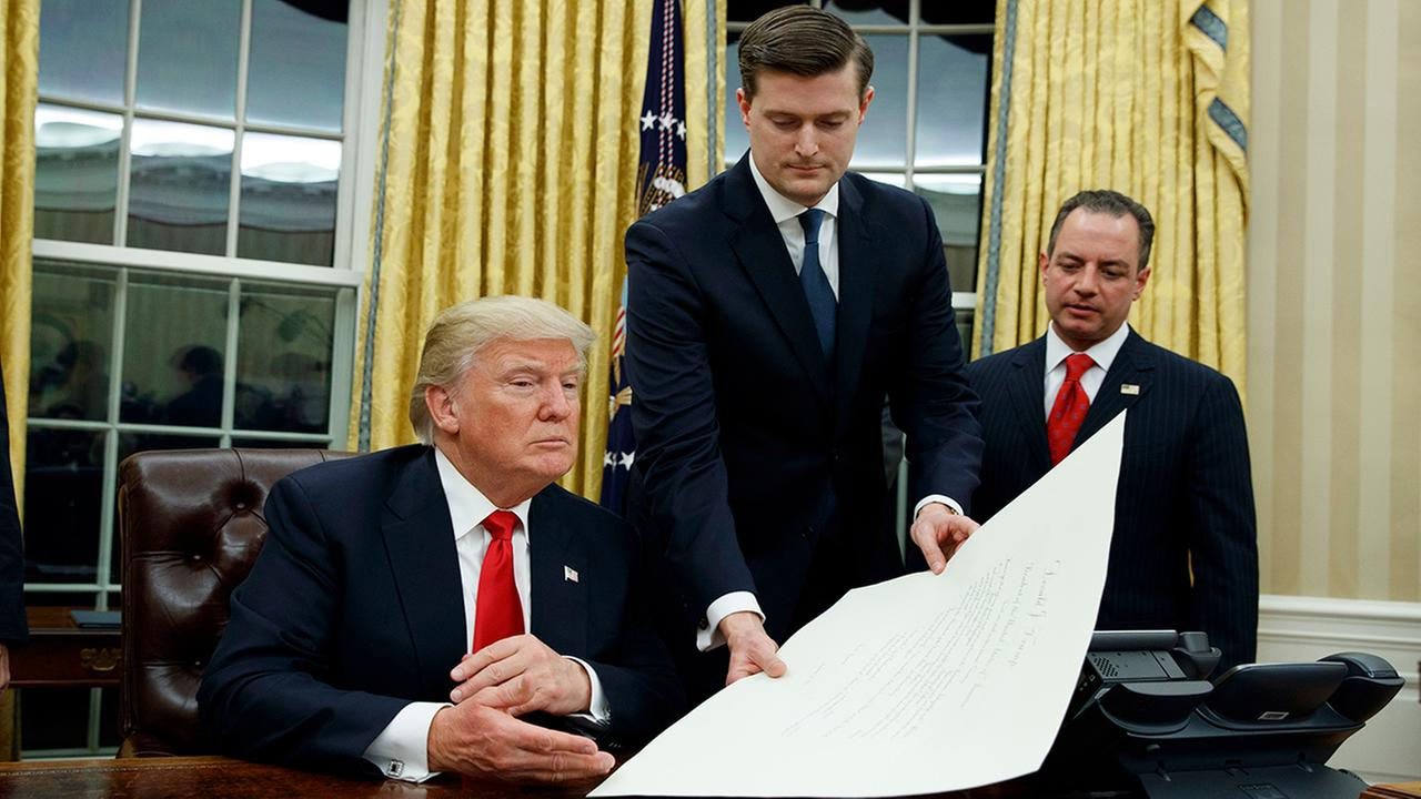 In this Jan. 20, 2017 photo, White House Staff Secretary Rob Porter, center, hands President Trump a confirmation order for James Mattis as defense secretary. (AP Photo/Evan Vucci)
