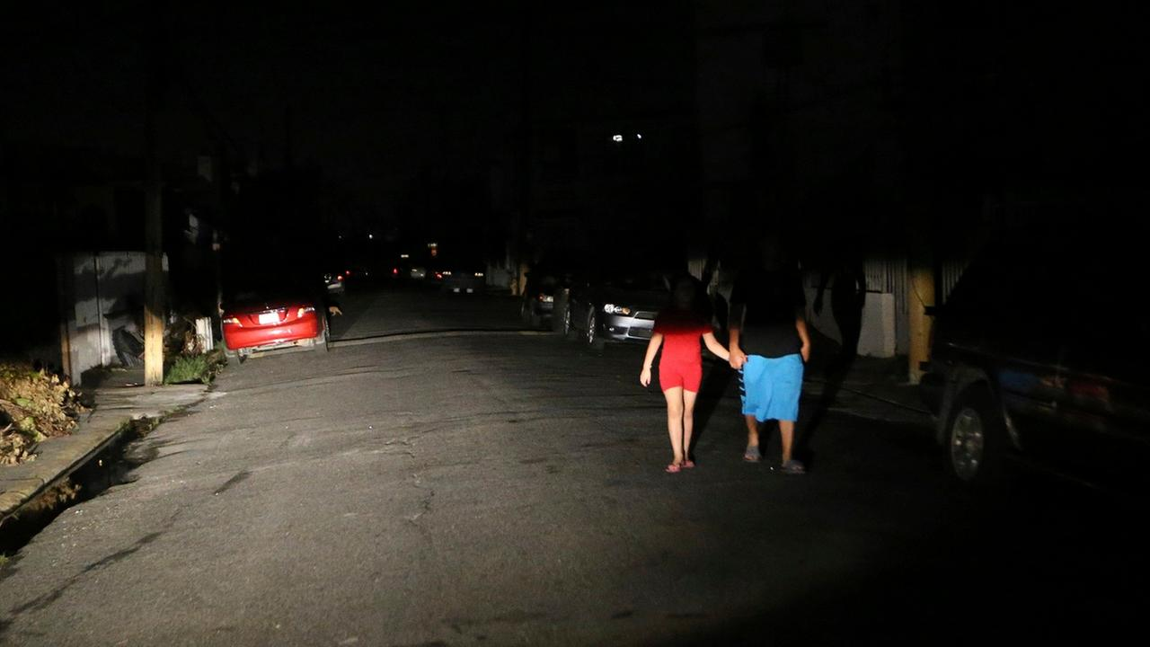 Raphael Urena&Viviana Urena, illuminated by  headlights from a car, walk down residential street, as most of Puerto Rico copes without electricity, in aftermath of Hurricane Maria