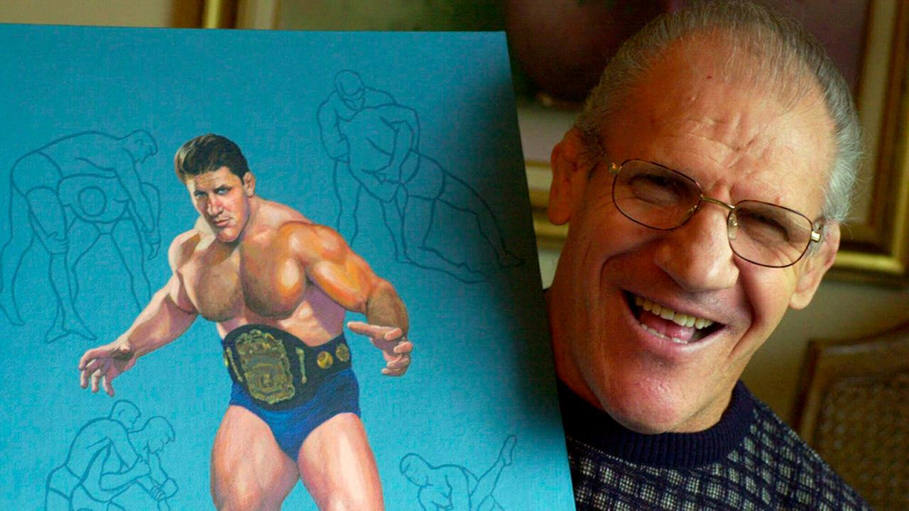 In this Nov. 30, 2000, photo, former pro wrestler Bruno Sammartino, then 65, poses with a painting of him in his pro wrestling prime at age 35