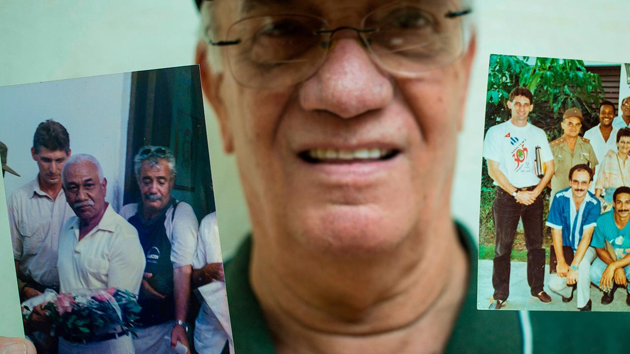 In this April 2, 2018 photo, radio journalist Normando Hernandez Castro, 70, shows pictures with himself with Miguel Mario Diaz-Canel Bermudez in Santa Clara, Cuba.