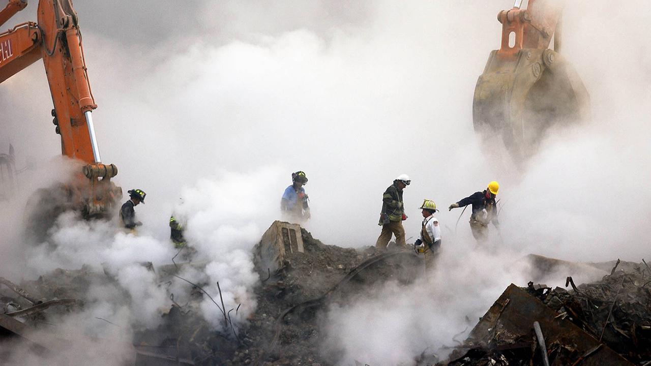 In this Oct. 11, 2001 file photo, firefighters make their way over the ruins and through clouds of smoke at the World Trade Center in New York.  (AP Photo/Stan Honda, Pool, File)