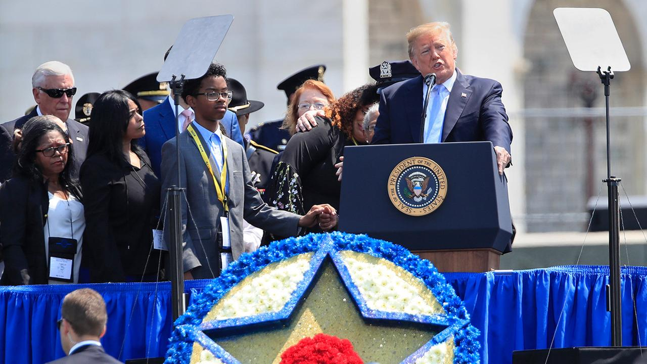 President Donald Trump, joined by the family of NYPD detective Miosotis Familia, who was killed in the line of duty, speaks at the National Peace Officers Memorial Service