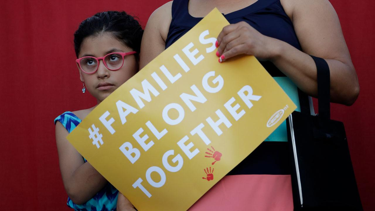 A girl stands with her mother during a rally to protest a new zero-tolerance immigration policy that has led to the separation of families on May 31 in San Antonio.