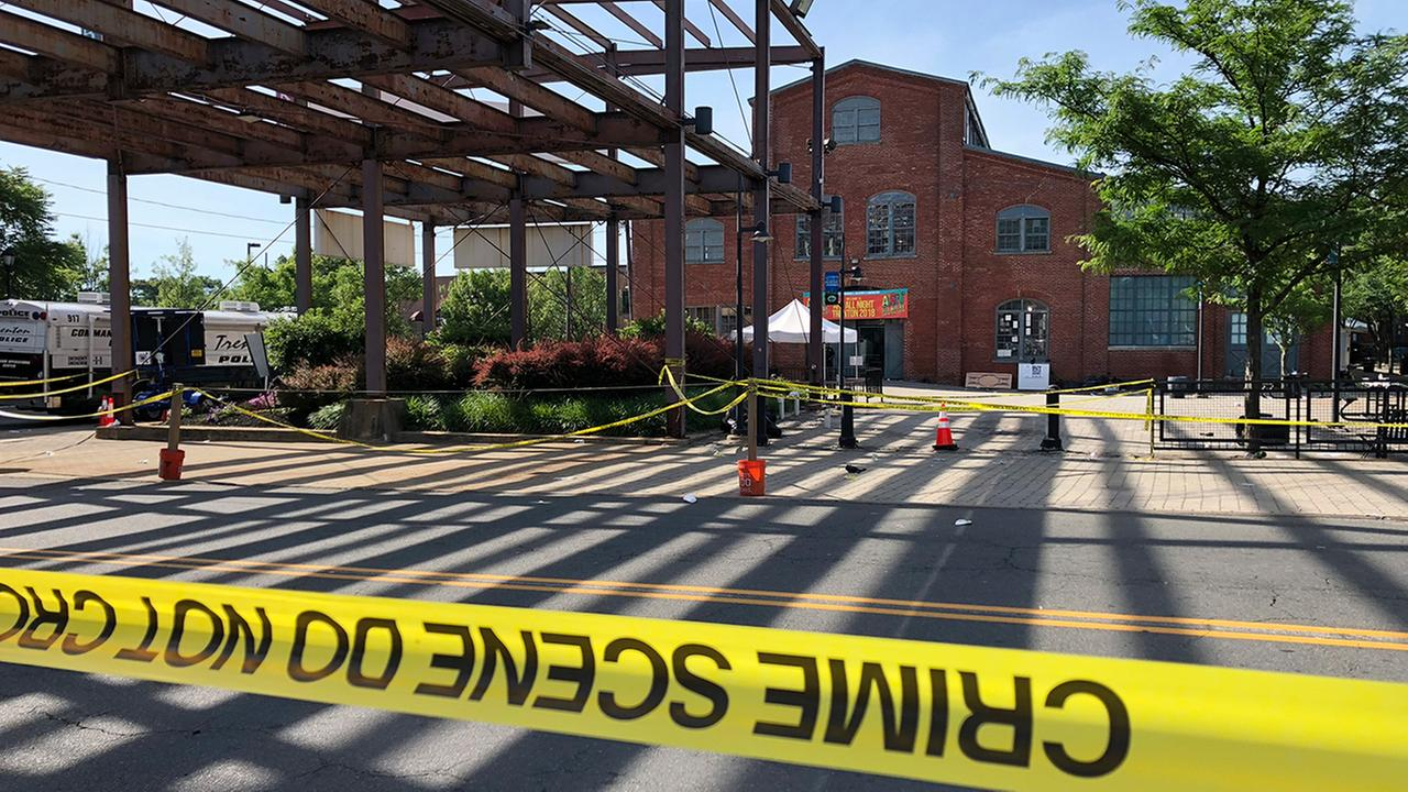 Police crime-scene tape keeps people away from the brick Roebling Wire Works building, background, in Trenton, N.J., hours after a shooting broke out there.(AP Photo/Mike Catalini)