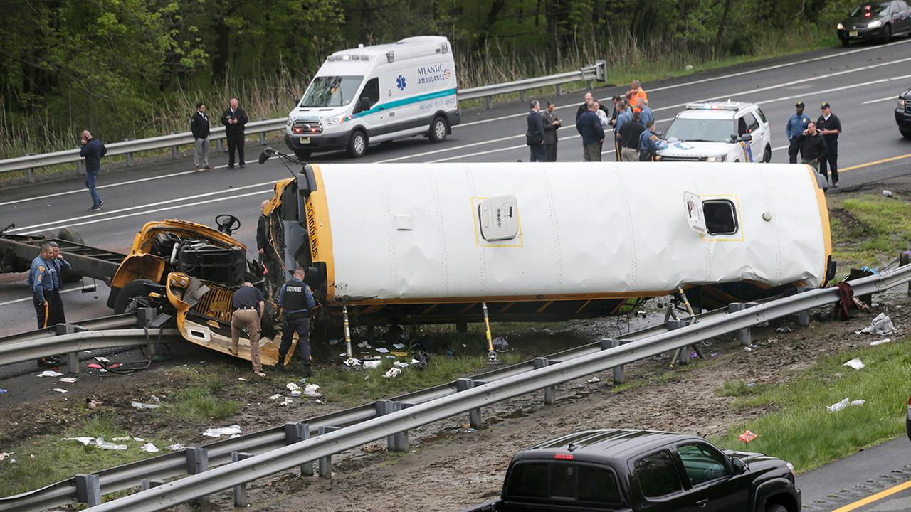 In this May 17, 2018, file photo, emergency personnel work at the scene of a school bus and dump truck collision on Interstate 80 in Mount Olive, N.J. (AP Photo/Seth Wenig, File)