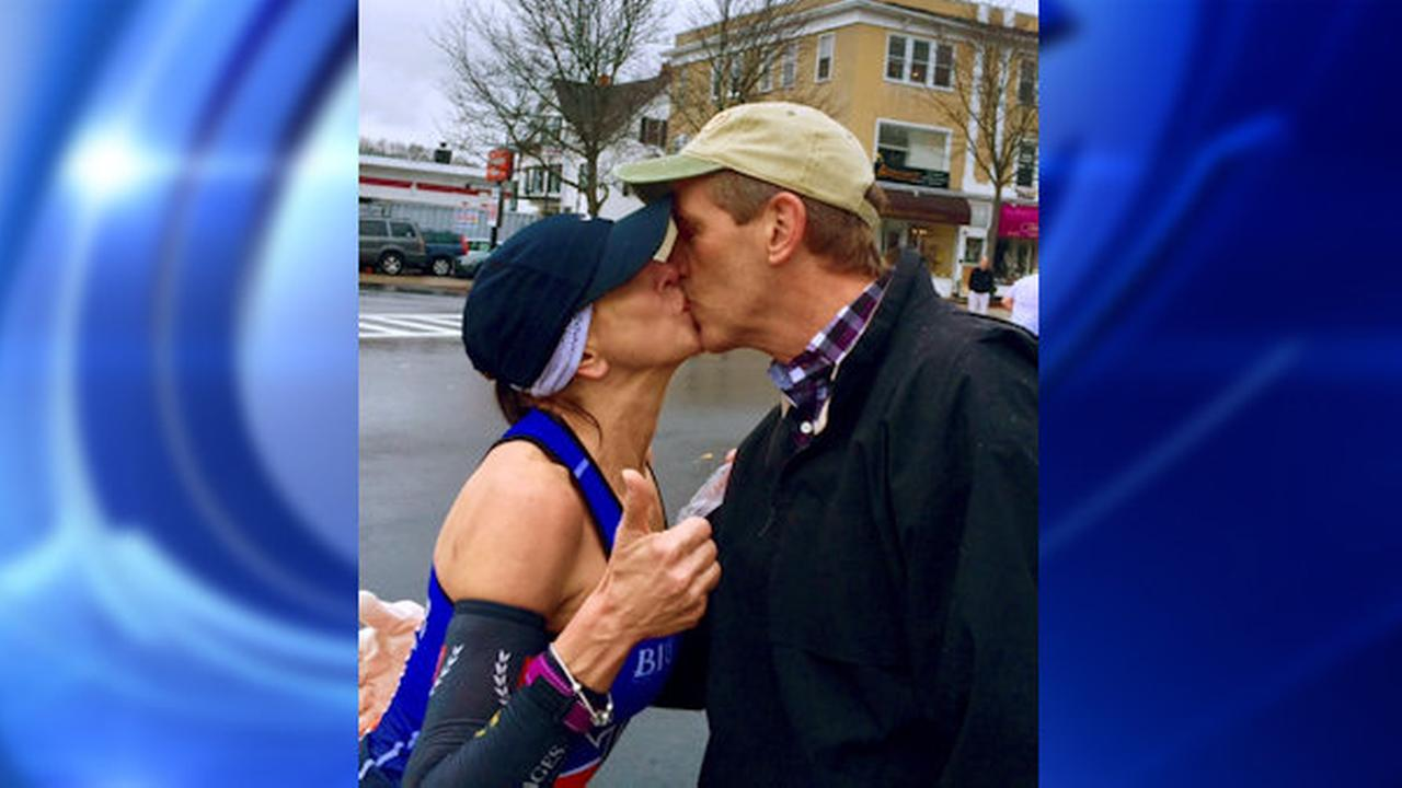 In this April 20, 2015 photo provided by Paige Tatge, her mother, Barbara Tatge, left, kisses an unknown spectator in Wellesley, Mass., as she ran in the Boston Marathon.