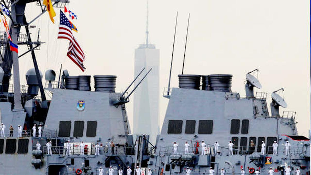 Sailors line the decks of the destroyer USS Cole as it glides past One World Trade Center, Wednesday, May 21, 2014 in New York.