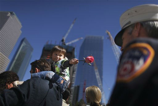 """<div class=""""meta image-caption""""><div class=""""origin-logo origin-image none""""><span>none</span></div><span class=""""caption-text"""">Luke Pavlenishzili, 2, riding on the shoulders of his father George Pavlenishzili, offers a rose to firefighter Joe Huber in 2010. (AP Photo/ Chang W. Lee)</span></div>"""