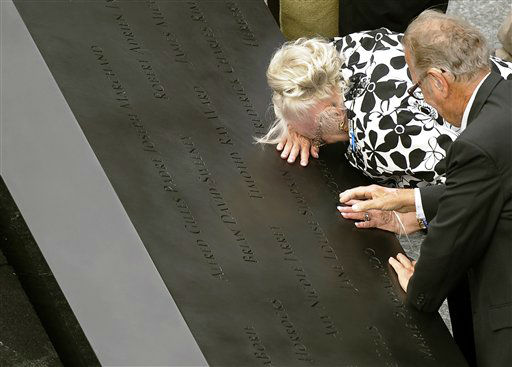 "<div class=""meta image-caption""><div class=""origin-logo origin-image none""><span>none</span></div><span class=""caption-text"">A woman cries over a name on the edge of the south pool during the ceremony marking the 10th anniversary of the attacks on the World Trade Center 2011. (AP Photo/ Timothy A. Clary)</span></div>"
