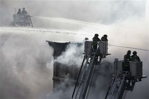 <div class='meta'><div class='origin-logo' data-origin='none'></div><span class='caption-text' data-credit='AP Photo/ John Minchillo'>Firefighters spray water on a collapsed building in New York's East Village, Thursday, March 26, 2015, in New York.</span></div>