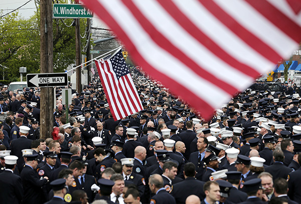 <div class='meta'><div class='origin-logo' data-origin='none'></div><span class='caption-text' data-credit='AP Photo/Seth Wenig'>Firefighters gather for the funeral of William Tolley in Bethpage, N.Y.</span></div>
