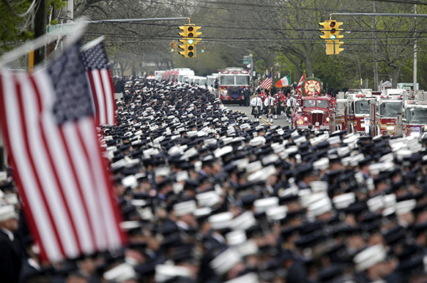 <div class='meta'><div class='origin-logo' data-origin='none'></div><span class='caption-text' data-credit='AP Photo/Seth Wenig'>Firefighters stand at attention as the funeral procession for William Tolley arrives at the church in Bethpage.</span></div>