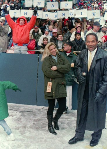 <div class='meta'><div class='origin-logo' data-origin='none'></div><span class='caption-text' data-credit='AP Photo/Ron Heflin, File'>O.J. Simpson stands with his wife Nicole Brown Simpson while broadcasting on the sidelines during the Thanksgiving Day NFL football game in 1993.</span></div>