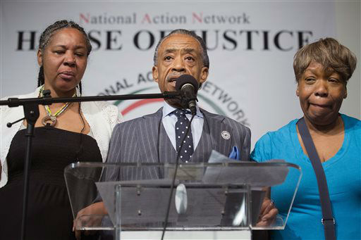 Rev. Al Sharpton speaks alongside Esaw Garner, wife of Eric Garner, left, and Gwen Carr, Eric Garner&#39;s mother, during a rally at the National Action Network headquarters. <span class=meta>(AP Photo&#47; John Minchillo)</span>