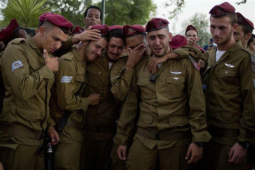 Israeli soldiers mourn over the grave of Sgt. Bnaya Rubel during his funeral at the military cemetery in Holon, Israel, Sunday, July 20, 2014.  <span class=meta>(AP Photo&#47; Ariel Schalit)</span>