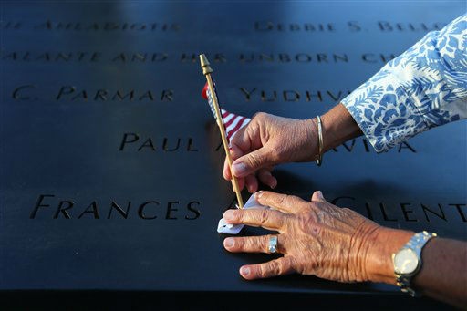 """<div class=""""meta image-caption""""><div class=""""origin-logo origin-image none""""><span>none</span></div><span class=""""caption-text"""">Judy Parisio places a small U.S. flag on the engraved name of her niece, Frances Ann Cilente, who worked and died at the World Trade Center, in 2012 (AP Photo/ Chang W. Lee)</span></div>"""