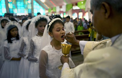 <div class='meta'><div class='origin-logo' data-origin='none'></div><span class='caption-text' data-credit='AP'>An Indian Catholic priest offers holy communion to Christian girls after Easter mass at a church in Gauhati, India. (AP Photo/Anupam Nath)</span></div>