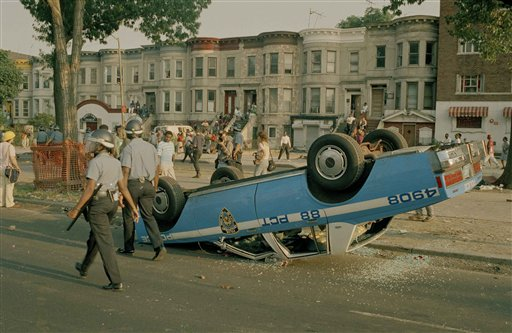 "<div class=""meta image-caption""><div class=""origin-logo origin-image none""><span>none</span></div><span class=""caption-text"">Police in riot gear walk past a police car that was overturned by rioters in the Crown Heights section of Brooklyn, New York, Aug. 21, 1991. (AP Photo/David Burns)</span></div>"