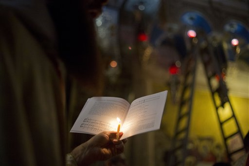 <div class='meta'><div class='origin-logo' data-origin='none'></div><span class='caption-text' data-credit='AP'>A Christian clergyman holds a candle and a holy book in Jerusalem's Old City, Sunday, March 27, 2016. (AP Photo/Ariel Schalit)</span></div>