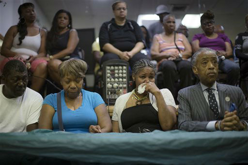 <div class='meta'><div class='origin-logo' data-origin='none'></div><span class='caption-text' data-credit='AP Photo/ John Minchillo'>Gwen Carr, mother of Eric Garner, center left, his wife Esaw Garner, center right, and Rev. Al Sharpton, right, attend a service at the Mount Sinai Center for Community Enrichment.</span></div>
