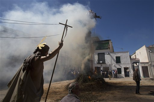 <div class='meta'><div class='origin-logo' data-origin='none'></div><span class='caption-text' data-credit='AP'>A religious figure is carried past a figure representing Judas burning on a cross in the village square in Tielmes, Spain, (AP Photo/Paul White)</span></div>