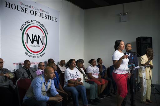 <div class='meta'><div class='origin-logo' data-origin='none'></div><span class='caption-text' data-credit='AP Photo/ John Minchillo'>Ellisha Flagg, sister of Eric Garner, speaks alongside the Rev. Al Sharpton, second from right, during a rally at the National Action Network headquarters.</span></div>
