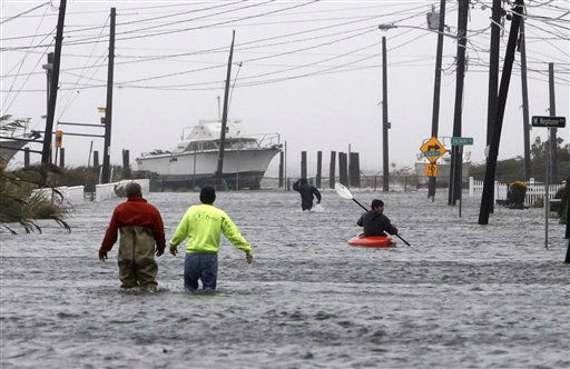 <div class='meta'><div class='origin-logo' data-origin='none'></div><span class='caption-text' data-credit='AP Photo/ Jason DeCrow'>People wade and paddle down a flooded street as Hurricane Sandy approaches, Monday, Oct. 29, 2012, in Lindenhurst.</span></div>