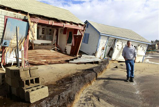 <div class='meta'><div class='origin-logo' data-origin='none'></div><span class='caption-text' data-credit='AP Photo/ Steven Senne'>A man walks past cottages damaged by superstorm Sandy on Roy Carpenter's Beach in the village of Matunuck, in South Kingstown, R.I. on Tuesday, Oct. 30, 2012.</span></div>