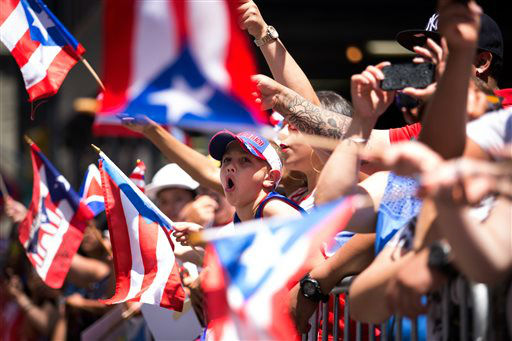 <div class='meta'><div class='origin-logo' data-origin='none'></div><span class='caption-text' data-credit='AP Photo/ Kevin Hagen'>Jaydden Garcia, 8, center, cheers as the annual National Puerto Rican Day Parade makes its way up New York's Fifth Ave. (AP Photo/Kevin Hagen)</span></div>