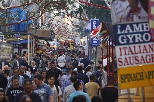 """<div class=""""meta image-caption""""><div class=""""origin-logo origin-image ap""""><span>AP</span></div><span class=""""caption-text"""">Crowds of people file file through a narrow corridor between food vendor and bars on Mulberry Street during the first day of the annual Feast of San Gennaro in Little Italy (AP)</span></div>"""