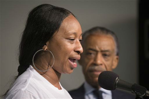 Ellisha Flagg, sister of Eric Garner, speaks alongside the Rev. Al Sharpton, right, during a rally at the National Action Network headquarters. <span class=meta>(AP Photo&#47; John Minchillo)</span>