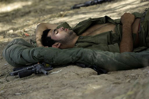 An Israeli soldier sleeps near the border of Israel and Gaza, Friday, July 18, 2014. Israeli troops pushed deeper into Gaza on Friday to destroy rocket launching sites and tunnels. <span class=meta>(AP Photo&#47; Tsafrir Abayov)</span>