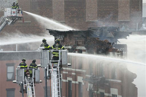 <div class='meta'><div class='origin-logo' data-origin='none'></div><span class='caption-text' data-credit='AP Photo/ John Minchillo'>New York City firefighters work the scene of a large fire and a partial building collapse in the East Village neighborhood of New York.</span></div>