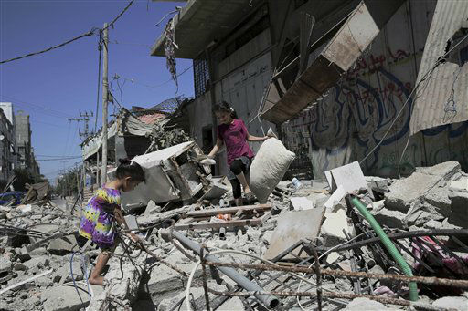 Palestinian girls collect their belongings of the al-Yazje family at a damaged apartment building which was hit by an overnight Israeli missile strike in Gaza City. <span class=meta>(AP Photo&#47; Adel Hana)</span>