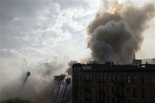 <div class='meta'><div class='origin-logo' data-origin='none'></div><span class='caption-text' data-credit='AP Photo/ John Minchillo'>New York City firefighters work the scene of a large fire and a partial building collapse in the East Village.</span></div>