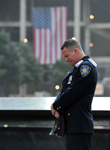 """<div class=""""meta image-caption""""><div class=""""origin-logo origin-image none""""><span>none</span></div><span class=""""caption-text"""">Daniel Henry, a Port Authority police officer, pauses during a moment of silence at 9:01 a.m. at the south reflecting pool in 2013. (AP Photo/ Stan Honda)</span></div>"""