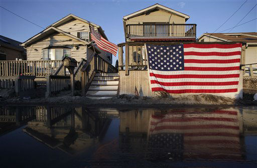 <div class='meta'><div class='origin-logo' data-origin='none'></div><span class='caption-text' data-credit='AP Photo/ Mark Lennihan'>United States flags are displayed on flood-damaged homes in the Breezy Point section of Queens, N.Y., Wednesday, Nov. 28, 2012.</span></div>