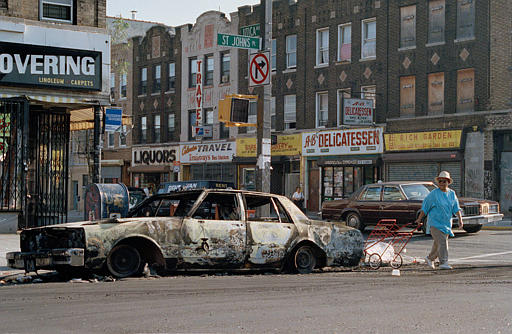 "<div class=""meta image-caption""><div class=""origin-logo origin-image none""><span>none</span></div><span class=""caption-text"">A woman passes a fire-bombed car as she crosses St. Johns Place on Utica Avenue in the Crown Heights sectioin of Brooklyn, Aug. 22, 1991. (AP Photo/David Cantor)</span></div>"
