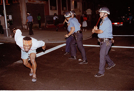 "<div class=""meta image-caption""><div class=""origin-logo origin-image none""><span>none</span></div><span class=""caption-text"">A protester in a crowd demanding that police leave Crown Heights runs for safety after being struck by police as the crowd marched down Utica Avenue, Aug. 23, 1991. (AP Photo/Bebeto Matthew)</span></div>"
