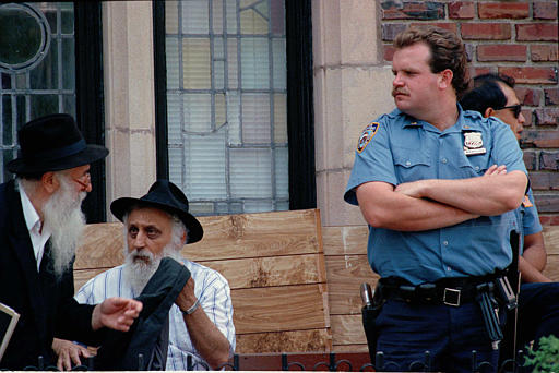 "<div class=""meta image-caption""><div class=""origin-logo origin-image none""><span>none</span></div><span class=""caption-text"">A New York City police officer stands guard as two Hasidic Jewish men go about their business in the Crown Heights neighborhood of Brooklyn, N.Y., Aug. 23, 1991. (AP)</span></div>"