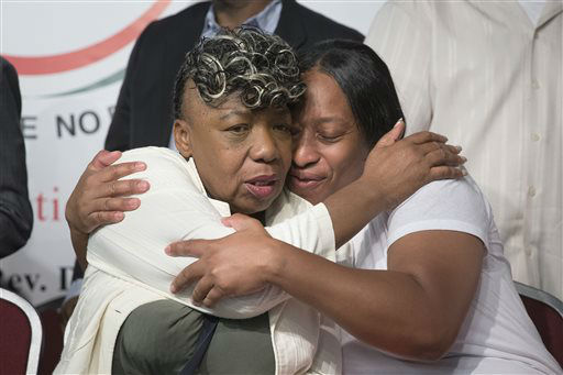 Gwen Carr, mother of Eric Garner, left, and his sister Ellisha Garner, hug during a rally at the National Action Network headquarters. <span class=meta>(AP Photo&#47; John Minchillo)</span>
