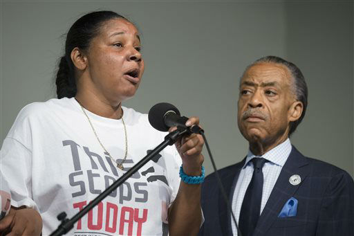 Esaw Garner, wife of Eric Garner, left, speaks alongside the Rev. Al Sharpton during a rally at the National Action Network headquarters. <span class=meta>(AP Photo&#47; John Minchillo)</span>