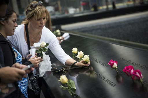"<div class=""meta image-caption""><div class=""origin-logo origin-image none""><span>none</span></div><span class=""caption-text"">A woman places flowers on the name of a loved one during memorial observances on the 13th anniversary of the Sept. 11 terror attacks on the World Trade Center. (AP Photo/ Andrew Burton)</span></div>"
