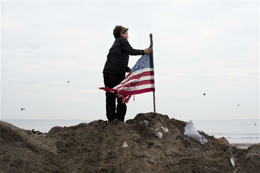 "<div class=""meta image-caption""><div class=""origin-logo origin-image none""><span>none</span></div><span class=""caption-text"">Matt Daly, 12, of Connecticut, places a U.S. flag atop a pile of sand removed from streets in the Rockaways, Saturday, Nov. 10, 2012, in the Queens borough of New York.  (AP Photo/ John Minchillo)</span></div>"
