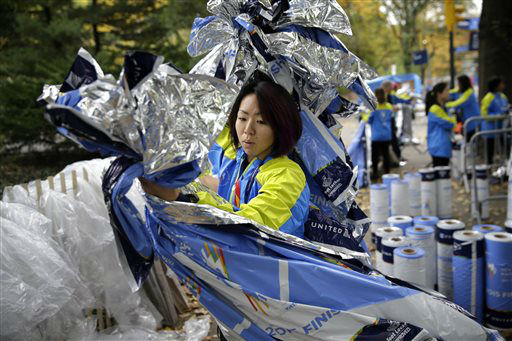 <div class='meta'><div class='origin-logo' data-origin='none'></div><span class='caption-text' data-credit='AP Photo/ Seth Wenig'>Volunteer Eri Miyasaka helps to arrange recovery blankets at the finish line before the start of the 2015 New York City Marathon.</span></div>