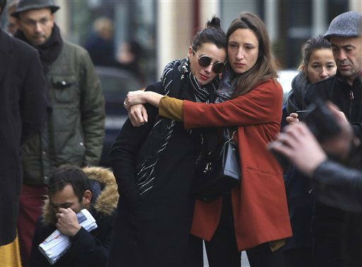 """<div class=""""meta image-caption""""><div class=""""origin-logo origin-image none""""><span>none</span></div><span class=""""caption-text"""">Women comfort each other as they stand in front of the Carillon cafe, in Paris, Saturday, Nov.14, 2015.  (AP Photo/ Thibault Camus)</span></div>"""