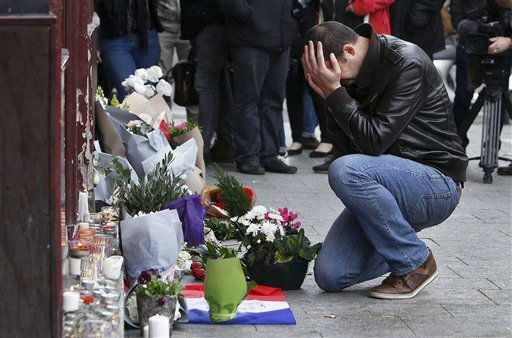 """<div class=""""meta image-caption""""><div class=""""origin-logo origin-image none""""><span>none</span></div><span class=""""caption-text"""">A man holds his head in his hands as he lays flowers in front of the Carillon cafe, in Paris, Saturday, Nov.14, 2015.  (AP Photo/ Thibault Camus)</span></div>"""